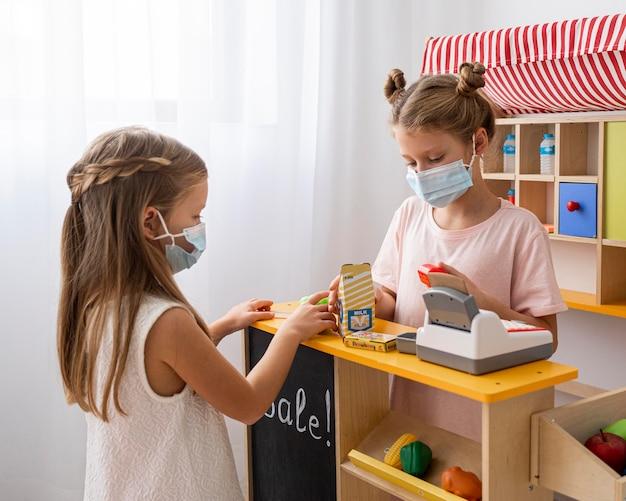 Kinder, die zusammen drinnen spielen, während sie medizinische masken tragen