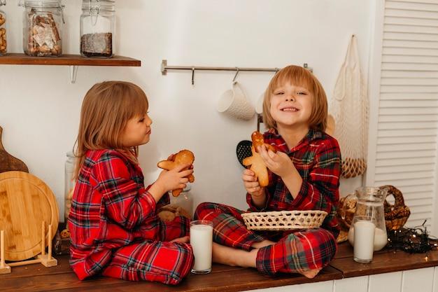 Kinder, die zusammen kekse am weihnachtstag essen