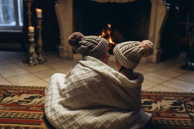 Kinder, die zusammen nahe kamin spielen, spaß in der winterzeit lächeln und haben. weihnachten, neues jahr, winterkonzept