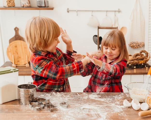Kinder, die zusammen weihnachtsplätzchen machen