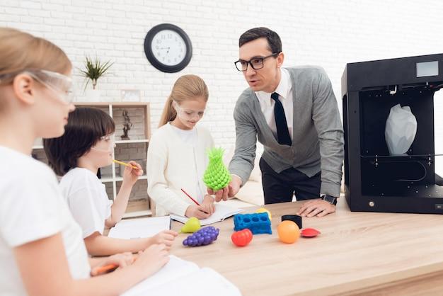 Kinder drucken mit einem lehrer verschiedene gegenstände auf einem 3d-drucker.