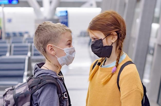 Kinder ein junge und ein mädchen am flughafen in einer schützenden gesichtsmaske