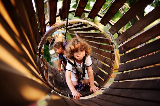 Kinder - ein junge und ein mädchen im seilpark passieren hindernisse. bruder und schwester klettern die seilstraße