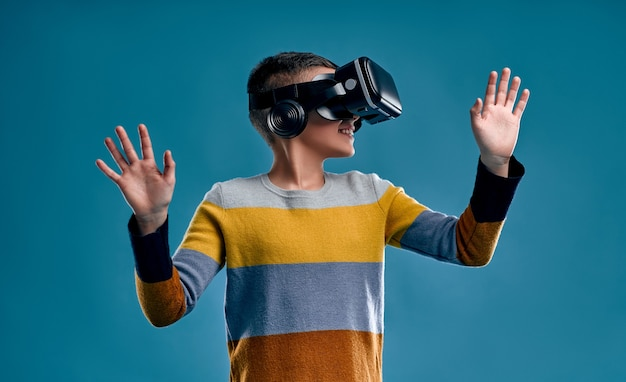 Kinder erleben virtuelle realität isoliert auf blauem hintergrund. überraschter kleiner junge, der in vr-brille schaut.