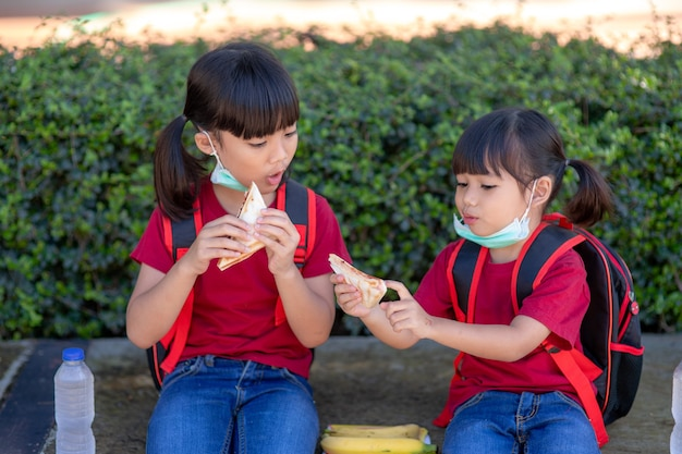 Kinder essen draußen in der schule. gesundes schulfrühstück für kinder. sandwich-zeit.