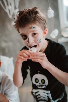 Kinder essen halloween-süßigkeiten auf einer kostümparty