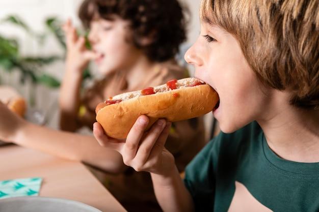 Kinder essen hot dogs zusammen