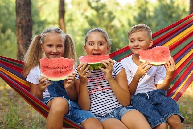 Kinder essen wassermelone und scherzen, an der frischen luft, sitzend auf einer hängematte