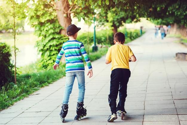 Kinder fahren auf roller und rollschuh auf der straße. rückansicht von freunden, die draußen zeit miteinander verbringen. aktiver outdoor-sport für kinder