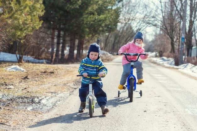 Kinder fahren im frühjahr fahrrad und runbike entlang der dorfstraße, wenn der schnee noch nicht geschmolzen ist