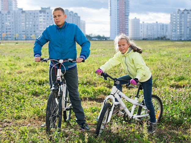 Kinder fahren mit dem fahrrad auf einer grünen wiese in der stadt