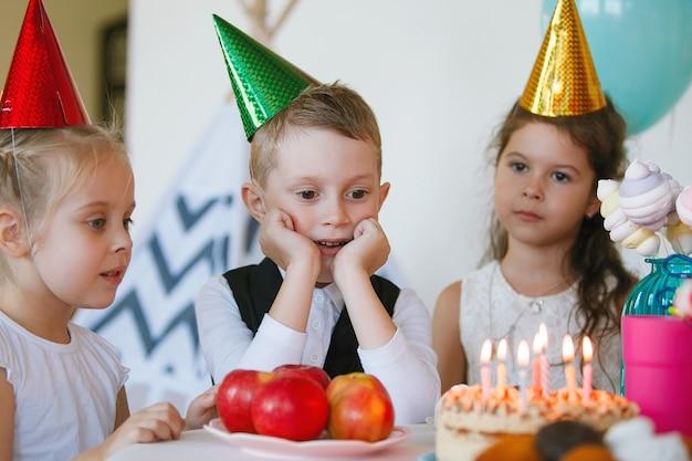 Kinder feiern ihren geburtstag mit einem kuchen mit kerzen