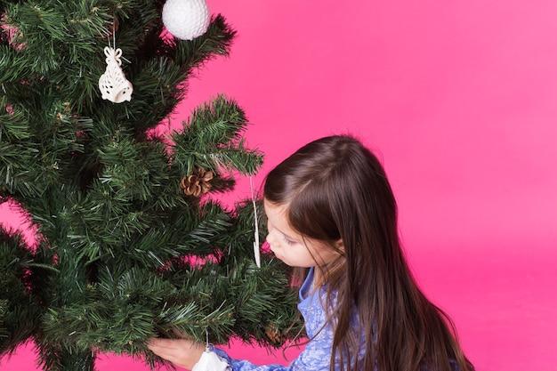 Kinder, feiertage und weihnachtskonzept - kleines mädchen, das weihnachtsbaum auf rosa oberfläche verziert