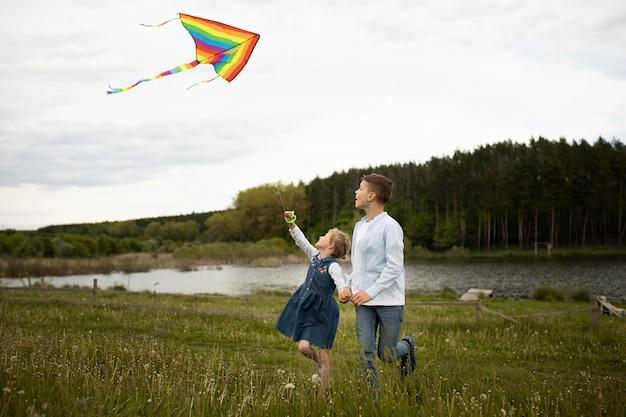 Kinder fliegen einen drachen mit vollem schuss