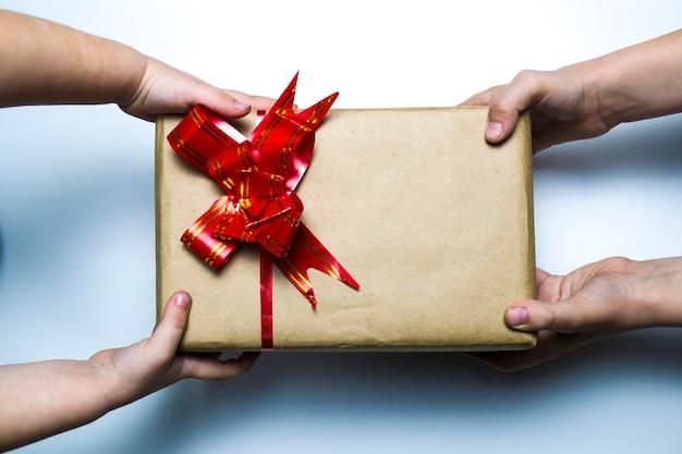 Kinder geben sich gegenseitig ein geschenk für das neue jahr auf einem weißen hintergrund der kinderhände