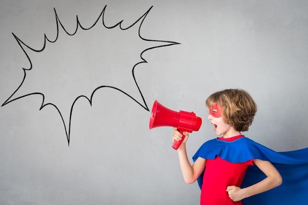 Kinder geben vor, superhelden zu sein. superheldenkind, das zu hause spielt fantasie und gewinnerkonzept