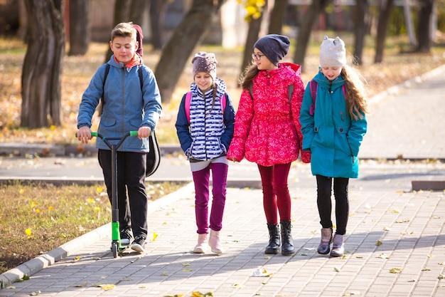 Kinder gehen mit einer lustigen gesellschaft auf dem bürgersteig zur schule.