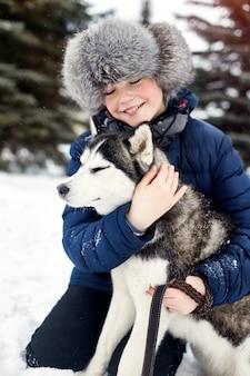 Kinder gehen raus und spielen im winter mit dem heiseren hund. kinder sitzen im schnee und streichelten hundeschlittenhund
