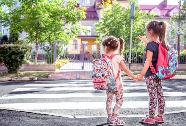 Kinder gehen zur schule, glückliche schüler mit schulrucksäcken und händchen haltend