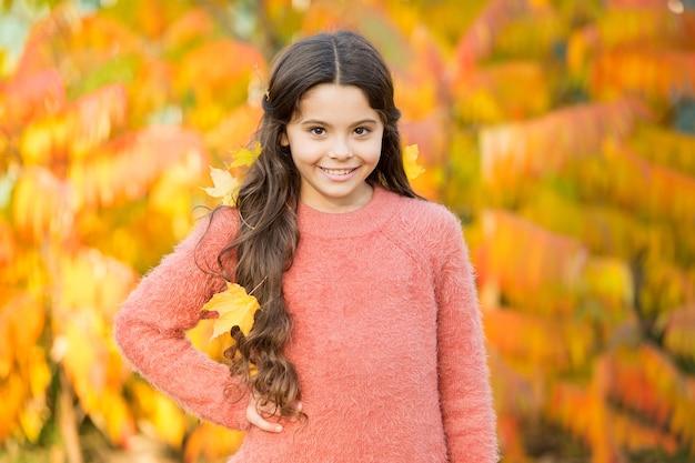Kinder genießen den herbst im freien. herbst treffen. kleines mädchen lächelt glückliches süßes kind wunderschöne lange haare ahornblätter. gemütlicher herbsttag. spielen sie mit blättern. glückliche kindheit. herbstfest. einfaches glück.