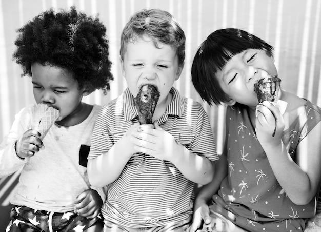 Kinder genießen eis an einem sommertag