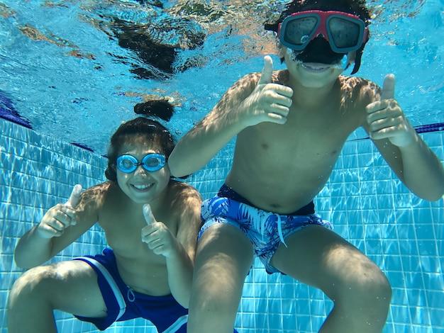 Kinder genießen im pool unter wasser
