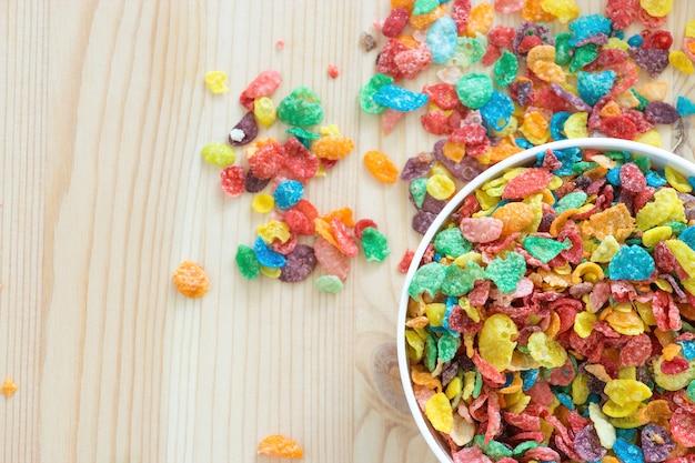 Kinder gesund schnelles frühstück. buntes reisgetreide auf hölzernem hintergrund. kopieren sie platz