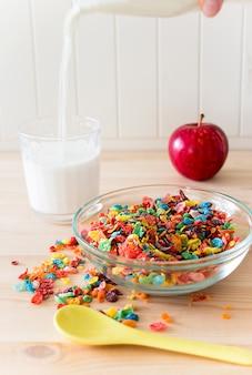 Kinder gesund schnelles frühstück. buntes reisgetreide, flüssige milch, apfel auf hölzernem hintergrund. kopieren sie platz