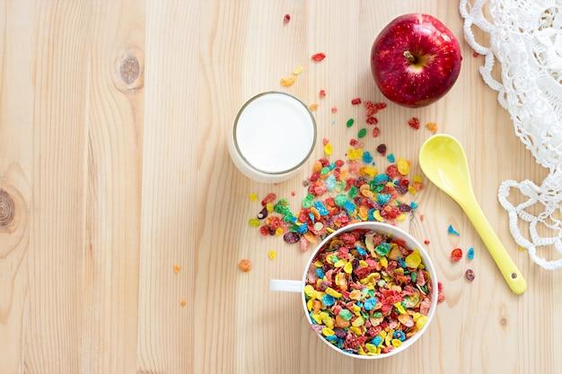 Kinder gesund schnelles frühstück. buntes reisgetreide, milch und roter apfel für kinder auf hölzernem hintergrund. kopieren sie platz