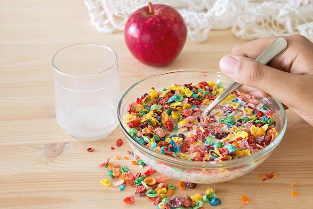 Kinder gesund schnelles frühstück. buntes reisgetreide mit milch und apfel für kinder auf hölzernem hintergrund. kopieren sie platz