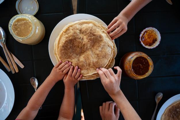 Kinder greifen beim frühstück nach crepes