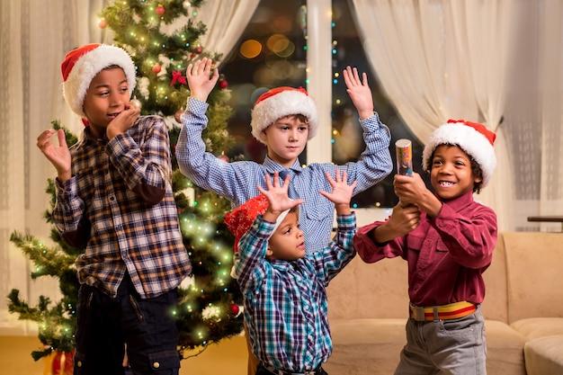Kinder haben angst vor weihnachtspetard. junge erschrocken freunde mit petard. der mutigste herr. unsere furchtlose cousine.