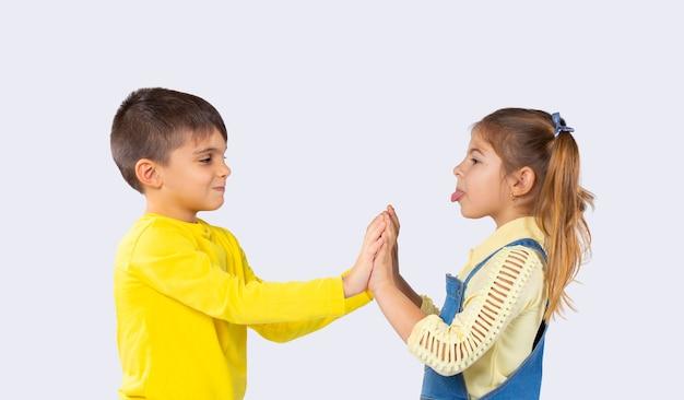 Kinder haben spaß. das mädchen zeigt dem jungen die zunge. weißer hintergrund. das konzept der emotionen und die zeit, die kinder verbringen.
