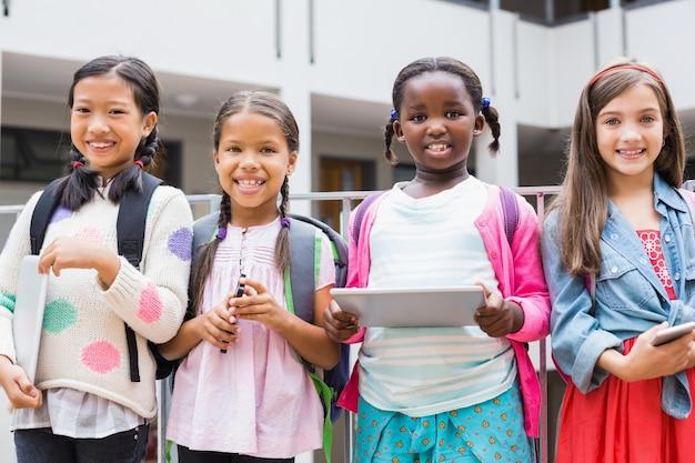 Kinder halten digitales tablet und handy auf der schulterrasse