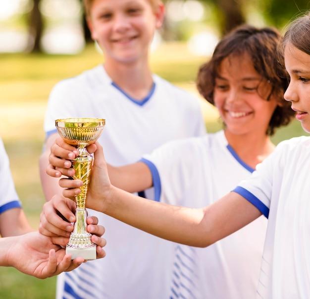 Kinder halten eine goldene trophäe
