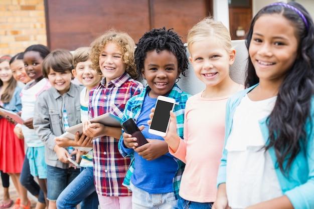 Kinder halten handy und digitales tablet auf schulterrasse