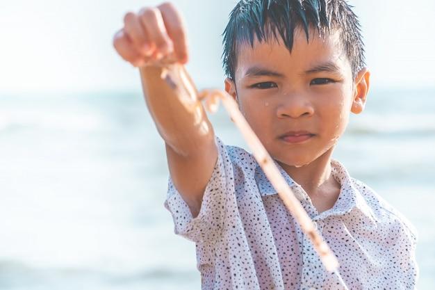 Kinder halten plastikstroh, das er am strand gefunden hat