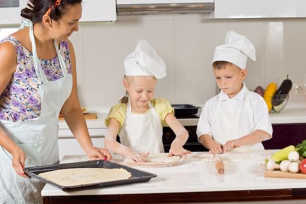 Kinder helfen ihrer mutter beim zubereiten des teigs