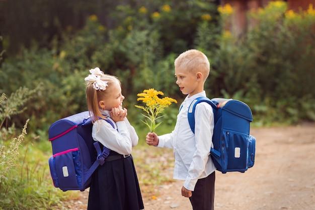 Kinder im alter von 7 bis 8 jahren, grundschüler mit rucksäcken und schuluniformen, ein junge schenkt einem mädchen blumen