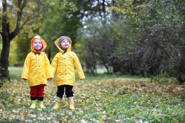 Kinder im herbstpark laufen tagsüber in regenmänteln