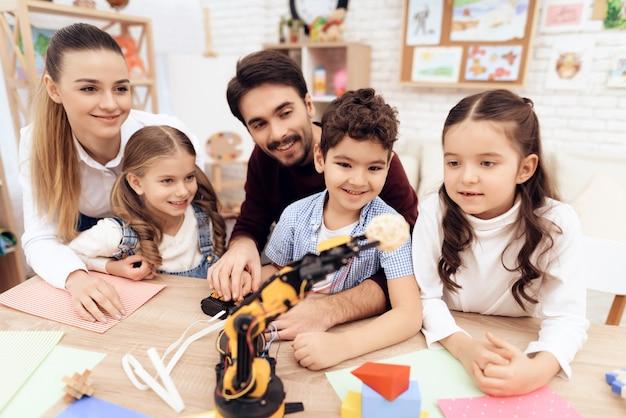 Kinder im kindergarten spielen mit roboter zusammen.