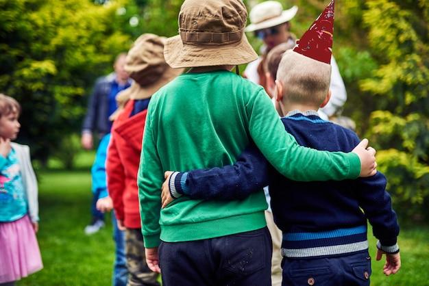 Kinder im kinderurlaub stehen mit den händen umarmt da