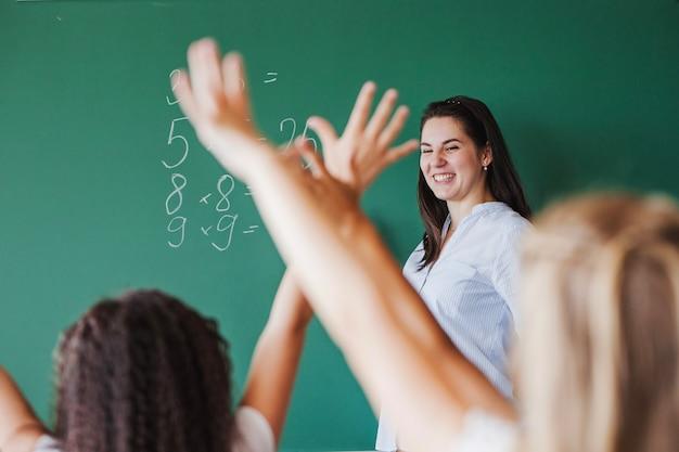 Kinder im klassenzimmer heben die hände