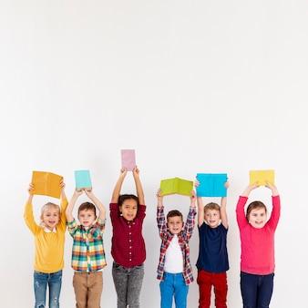 Kinder im kopierraum, die bücher über köpfen halten