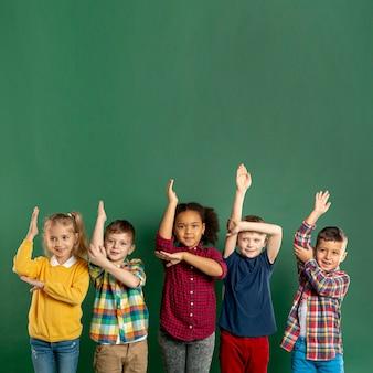 Kinder im kopierraum mit erhobenen armen