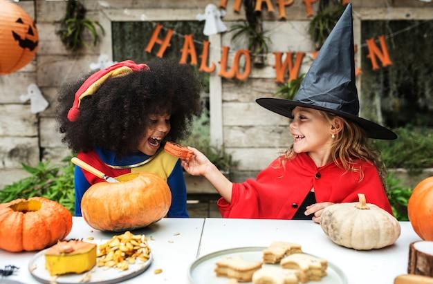 Kinder im kostüm, welches die halloween-jahreszeit genießt