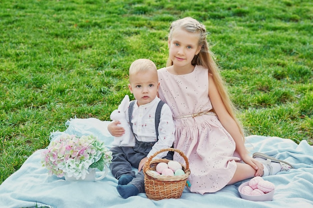 Kinder im park auf ostern picknick mit eiern und kaninchen