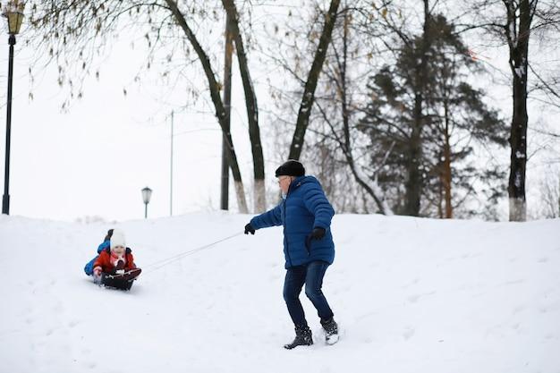 Kinder im park im winter. kinder spielen mit schnee auf dem spielplatz. sie formen schneemänner und rutschen die hügel hinab.