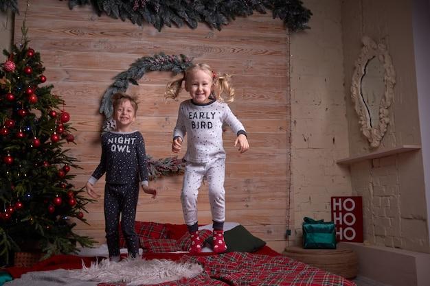Kinder im pyjama, die am weihnachtsfeiertagsabend zu hause spielen. glückliches kind, das auf das bett springt.