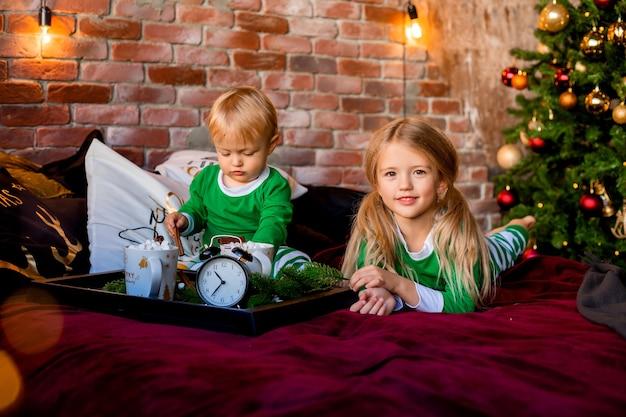Kinder im pyjama mit kakao in der nähe von weihnachtsbaum